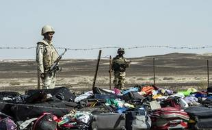Egyptian army soldiers stand guard next to the luggage and belongings of passengers of the A321 Russian airliner piled up at the site of the crash in Wadi el-Zolmat, a mountainous area in Egypt's Sinai Peninsula on November 1, 2015. International investigators began probing why a Russian airliner carrying 224 people crashed in Egypt's Sinai Peninsula, killing everyone on board, as rescue workers widened their search for missing victims. AFP PHOTO / KHALED DESOUKI