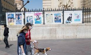 Des promeneurs passent devant les affiches des candidats aux municipales à Marseille, en avril 2020.