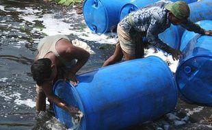Des hommes nettoient des containers remplis de substances toxiques dans une rivière du Bangladesh, à Dhaka en mai 2007.