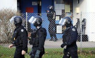 Des membres du GIPN accompagnent des enfants à l'extérieur de l'école de maternelle où une prise d'otages a eu lieu le 13 décembre 2010 à Besançon (Doubs).