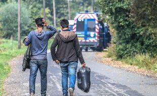 Deux migrants marchent sur le bord de la route après l'évacuation d'un campement sauvage près de Grande-Synthe en septembre 2017.
