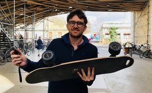 Quentin Sartorius avec son skate et sa télécommande à la main.