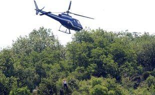 Un hélicoptère de la gendarmerie nationale hélitreuille un membre des  secouristes de l'endroit où le corps carbonisé de la joggeuse Marie-Jeanne a été retrouvé le  22 juin 2011 sur les hauteurs de Tournon-sur-Rhône (Ardèche).