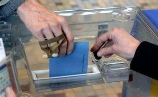Une personne introduit son bulletin de vote dans une urne.