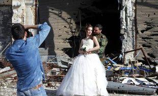 Des nouveaux mariés prennent la pose le 5 février 2016 devant le photographe Jaafar Merhi au milieu des façades soufflées par les explosions dans la ville de Homs
