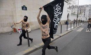 Des militantes Femen amènent devant la Grande Mosquée de Paris un drapeau présenté comme «salafiste» avant d'y mettre le feu, le 3 avril 2013.