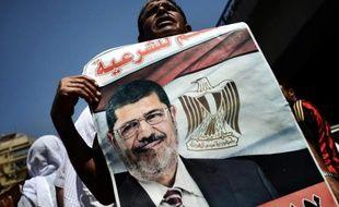 Ce partisan de Mohammed Morsi montre un portrait du président destitué lors d'une manifestation au Caire le 30 août 2013