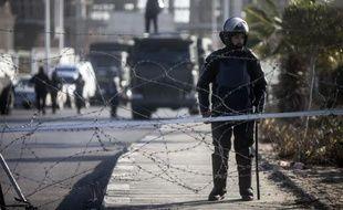 Des policiers anti-émeute postés devant l'académie de police du Caire où comparaît l'ancien président Mohamed Morsi, le 28 janvier 2014