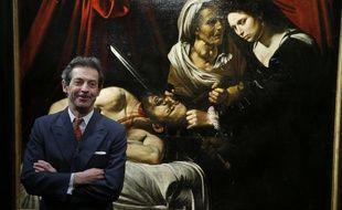 """L'expert Eric Turquin pose devant le tableau du Caravage """"Judith et Holopherne"""", authentifié par des experts, le 12 avril 2016 à Paris."""
