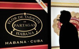 Un homme fume un cigare pendant le dîner d'ouverture du 16e Festival international du cigare à La Havane, Cuba, le 24 février 2014.