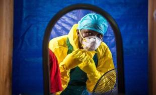 FILE - In this Thursday, Oct. 16, 2014 file photo, a healthcare worker dons protective gear before entering an Ebola treatment center in the west of Freetown, Sierra Leone.  Dr. Brima Kargbo, Sierra Leone's chief medical officer, confirmed Thursday Dec. 18, 2014, that Dr. Victor Willoughby died earlier in the day after being tested positive for Ebola on Saturday, the 11th doctor in the country to die from the disease that is ravaging West Africa. (AP Photo/Michael Duff, FILE)/NIN103/176114527499/AN OCT. 16, 2014 FILE PHOTO/1412181158
