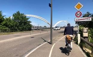 Un cycliste quitte Strasbourg et arrive sur le Pont de l'Europe. Au bout, la ville-frontière de Kehl... où un contrôle policier l'attend.