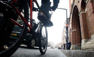 Un cycliste et une voiture dans le centre ville de Toulouse (illustration).