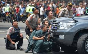 Des policiers indonésiens s'abritent derrière un véhicule alors que des explosions ont retenti à Djakarta, le 14 janvier 2016.