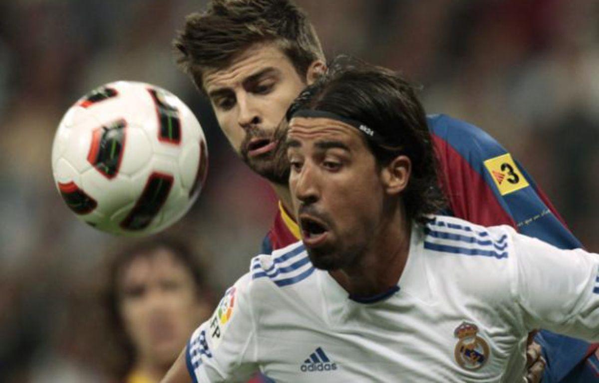 Le défenseur du Real Madrid Sami Khedira (en blanc) à la lutte avec celui du FC Barcelone, Gerard Pique, lors du clasico du 16 avril 2011 à Madrid. – S.Vera/REUTERS