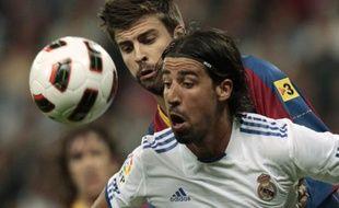 Le défenseur du Real Madrid Sami Khedira (en blanc) à la lutte avec celui du FC Barcelone, Gerard Pique, lors du clasico du 16 avril 2011 à Madrid.