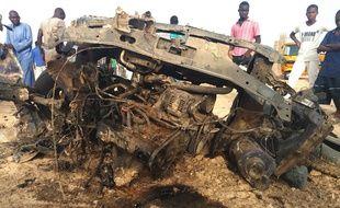 Des Nigérians regardent la carcasse d'un véhicule après un affrontement entre l'armée et Boko Haram le 27 avril 2018 (image d'illustration).