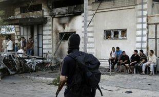 Des palestiniens se rassemblent autour d'une voiture brûlée le 19 juillet 2015, après cinq attentats coordonnés qui visaient des membres du Hamas et du Jihad islamique à Gaza