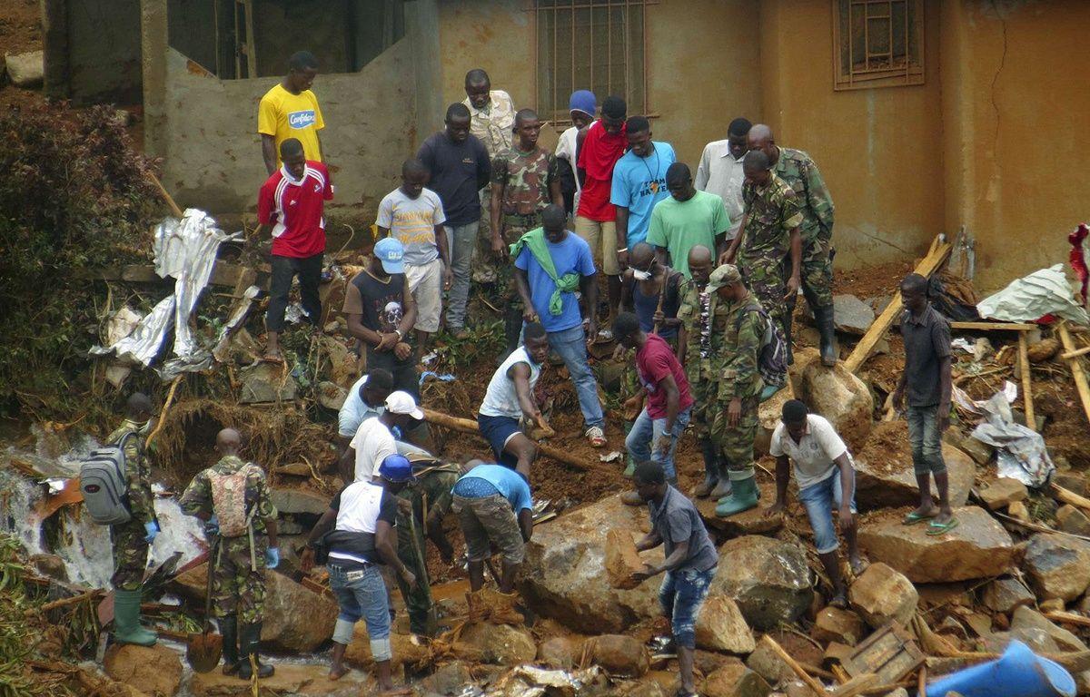 Des volontaires creusent à la recherche des corps après les inondations et coulées de boue à Freetown en Sierra Leone le 15 août 2017. – Manika Kamara/AP/SIPA