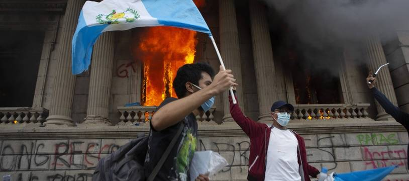 Devant le parlement en feu, un manifestant brandit le drapeau du Guatemala, le 21 novembre 2020.