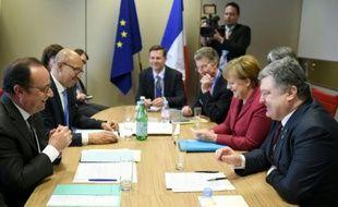 Le président François Hollande (g) s'entretient le 17 mars 2016 avec le président ukrainien, Petro Porochenko (d) et la chancelière allemande, Angela Merkel, à Bruxelles
