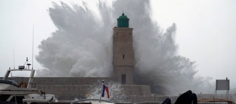 TOPSHOT - A wave breaks against a pier and a lighthouse as storm Ana smashes into France in Cassis on December 11, 2017, southeastern France.   / AFP PHOTO / BORIS HORVAT