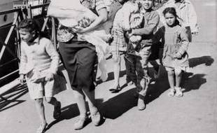 """Une femme et ses enfants désireux de gagner la métropole viennent de débarquer du """"Ville d'Oran"""" à Marseille le 26 mai 1962 comme de nombreux réfugiés notamment des Européens d'Algérie (pieds noirs) et des familles de harkis qui continuent d'affluer vers la France depuis la signature des accords d'Evian. Après plus de sept ans de guerre l'Algérie a proclamé son indépendance après la signature des accords d'Evian le 18 mars 1962 et leur ratification par référendum en France le 08 avril 1962 puis en Algérie le 1er juillet 1962."""