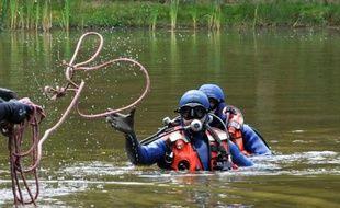 Des gendarmes sondent un étang à Chénérailles le 29 août 2014, à la recherche d'un bébé disparu
