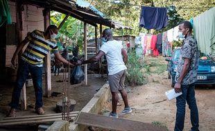 Des bénévoles distribuent de l'aide alimentaires aux familles dans le besoin à Cayennes, en Guyane durement frappée par le coronavirus et confinée depuis des mois.