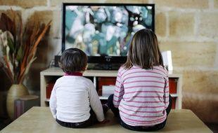 Deux enfants regardent un écran de télévision.