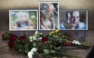 Des fleurs déposées le 1er aout 2018 à Moscou près des portraits d'Alexander Rastorguyev, Kirill Radchenko et Orkhan Dzhemal, trois journalistes tués le 30 juillet 2018 en Centrafrique.