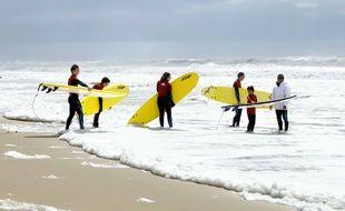 Des surfeurs sur une plage de Lacanau.