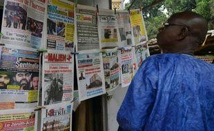 Un homme regarde les unes des journaux maliens, le 23 novembre 2015 à Bamako
