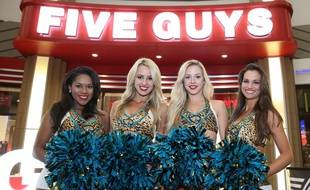 Des pom-pom girls devant un restaurant Five Guys