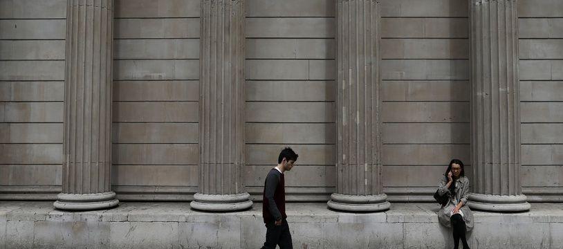 Un homme marche devant la banque d'Angleterre, à la City de Londres.
