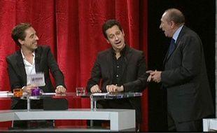 Capture vidéo de Gérard Collomb (à dr.) et de Laurent Gerra (au centre) chantant Eddy Mitchell. Emission diffusée sur Paris Première le 26 novembre 2010.