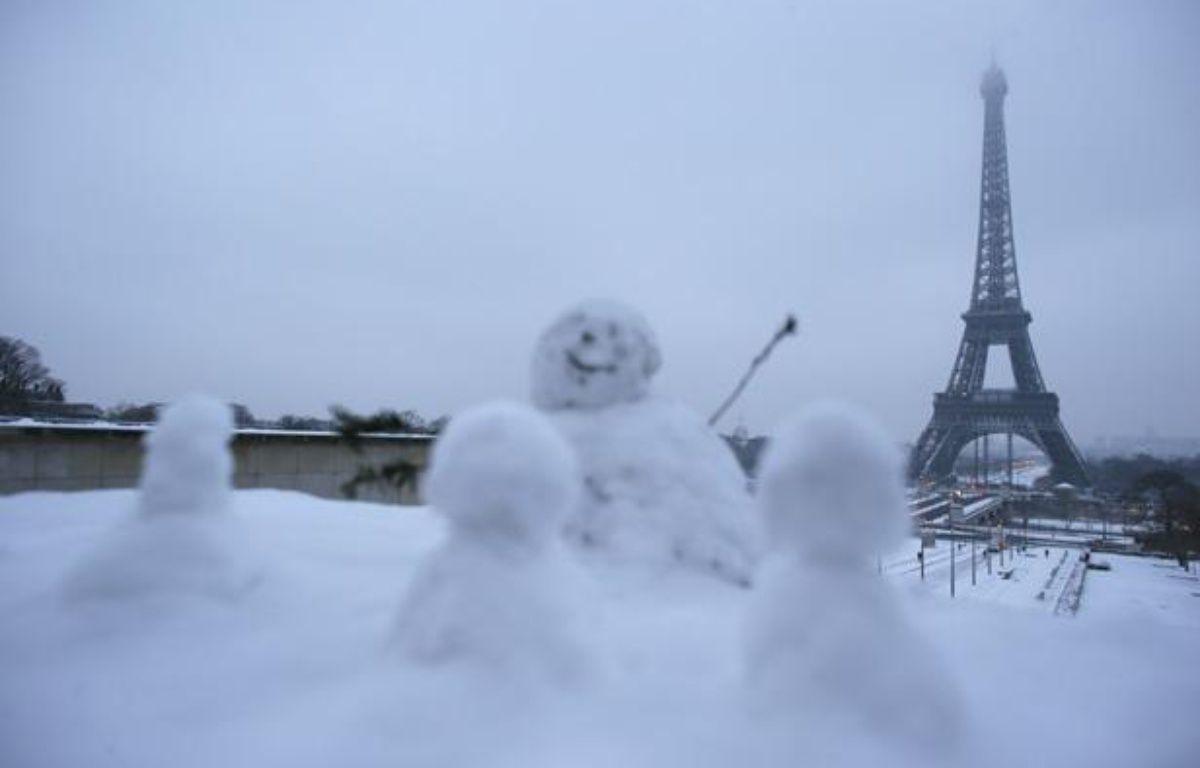 Des enfants ont sculpté des bonhommes de neige face à la Tour Eiffel, le 19 janvier 2013. – KENZO TRIBOUILLARD / AFP