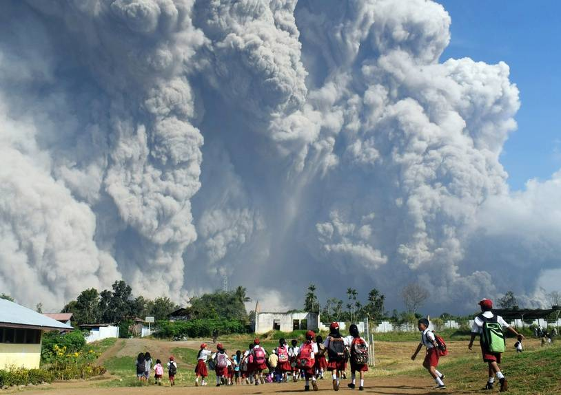 Indonesian schoolchildren walk together at Sipandak elementary school in Tiga Pancur village in Karo, North Sumatra on February 19, 2018, as thick volcanic ash from Mount Sinabung volcano rises into the air following another eruption. Sinabung roared back to life in 2010 for the first time in 400 years and has remained highly active since.