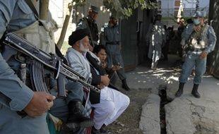 Des policiers afghans montent la garde à l'extérieur d'un bureau de vote de Kaboul le 18 septembre 2010.