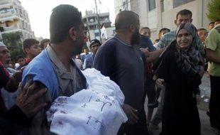 Un Palestinien porte le corps de sa fille de 5 ans, tué lors d'un raid israélien à Rafah, le 4 août 2014