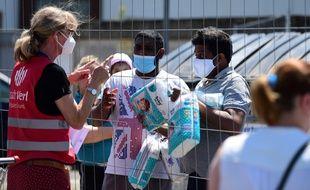 Des secouristes donnent des produits de première nécessité à des Allemands en quarantaine.