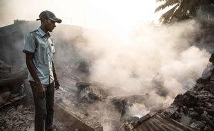 Un homme devant les ruines d'une maison encore fumante, dans le quartier PK5 le 26 décembre 2019.
