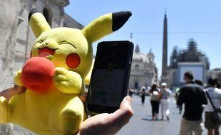 Un joueur tient une mascotte de Pokémon et joue au Pokémon Go sur son portable, le 19 juillet 2016 à Rome.