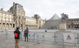 Des touristes devant le musée du Louvre fermé, à Paris le 28 décembre 2020.