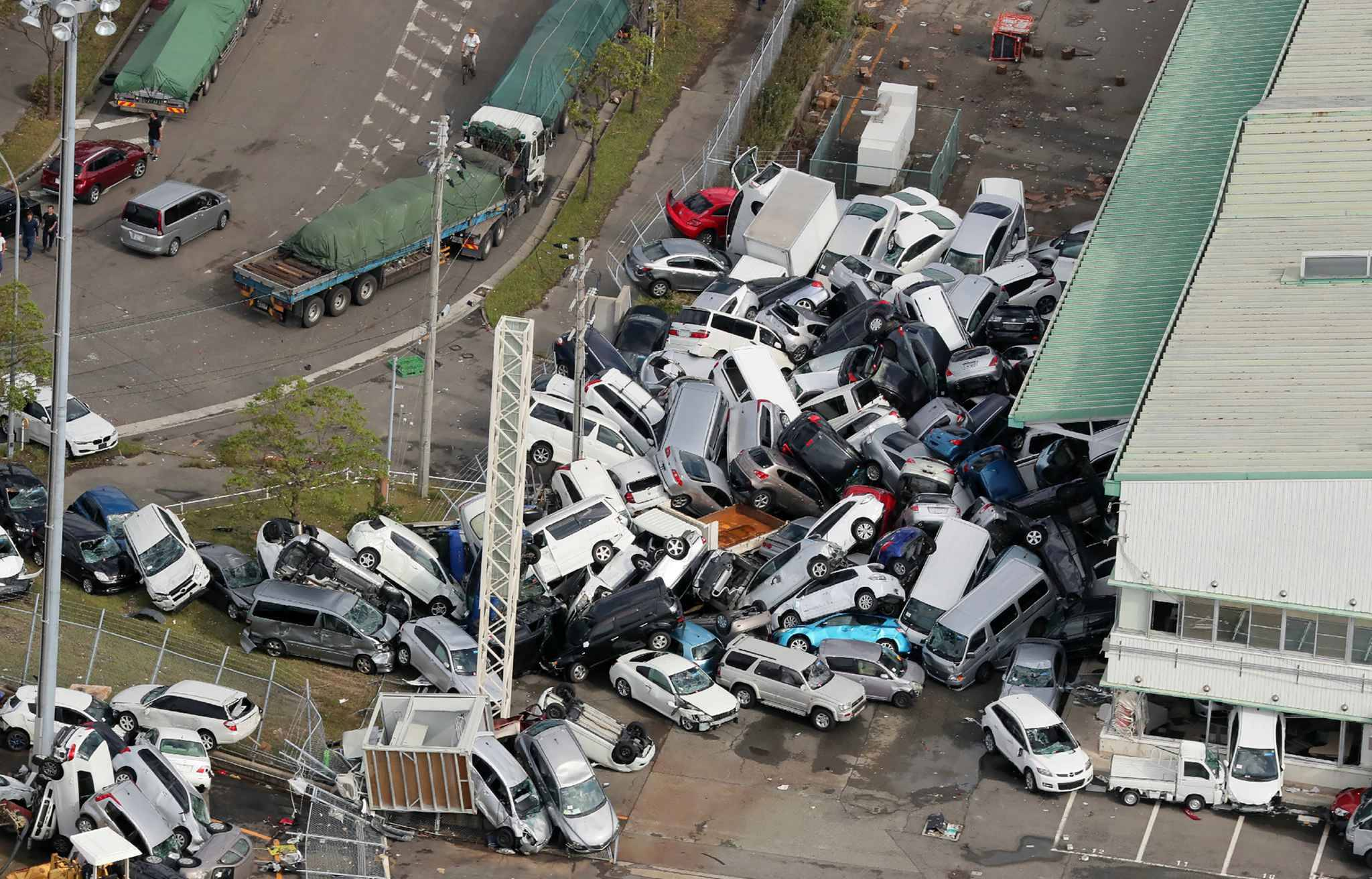 An aerial view from a Jiji Press helicopter shows vehicles piled in a heap due to strong winds in Kobe, Hyogo prefecture on September 5, 2018, after typhoon Jebi hit the west coast of Japan. The toll in the most powerful typhoon to hit Japan in a quarter century rose on September 5 to nine, with thousands stranded at a major airport because of storm damage.