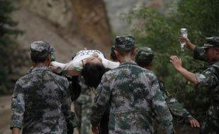 Des secouristes chinois portent un homme blessé après un tremblement de terre à Zhaotong au sud-ouest de la Chine le 3 août 2014
