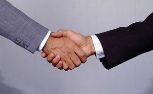 Une poignée de mains entre un jeune et un recruteur