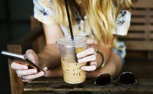 Illustration d'une femme regardant un smartphone avec un café à la main