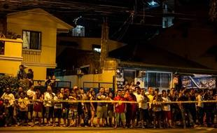 Photo prise le 19 juillet 2016, montrant des Philippins regarder les corps de deux dealers présumés, à Manille.