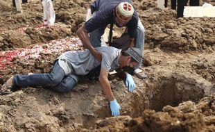 Un homme tombe au sol alors qu'il pleure lors de l'enterrement d'un parent décédé du Covid-19 au cimetière de Rorotan à Jakarta, en Indonésie, le mercredi 7 juillet 2021.